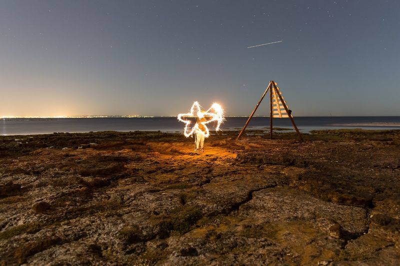 The Golden Star 43 Golden Moments Enjoying The Sights Bright Lights EyeEm Best Shots Night View Long Exposure Writing On The Walls Outdoors Horizon Over Water Beachside Star EyeEm Nature Lover Coastline Rock And Sea
