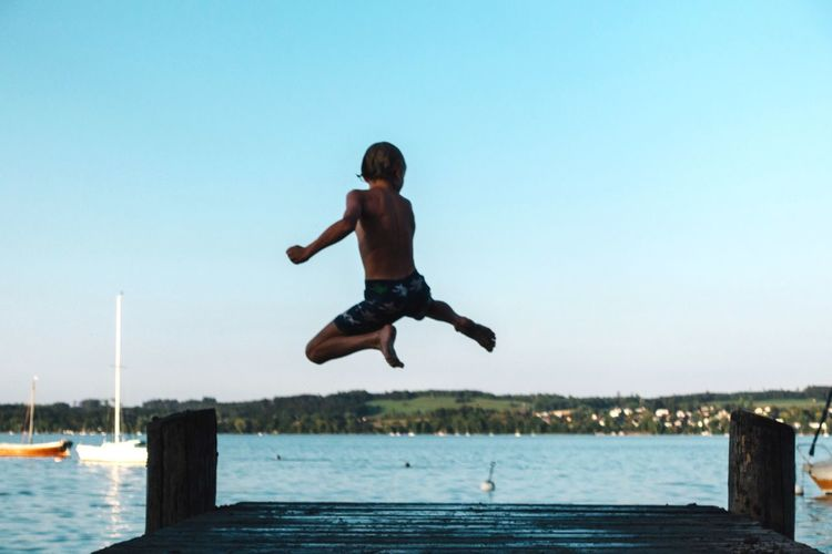 Full of life... Joy Fresh Summertime Summer Youth Jumping Water Mid-air Full Length One Person Sky Men Nature Leisure Activity Motion Lifestyles Shirtless Outdoors