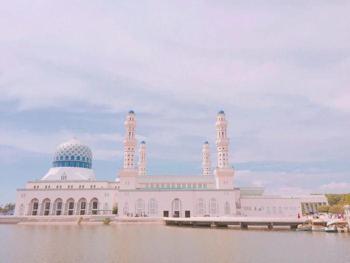Sabah state mosque by lake against cloudy sky