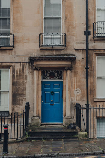 Bright blue front door on a traditional limestone terraced house in bath, somerset, uk.