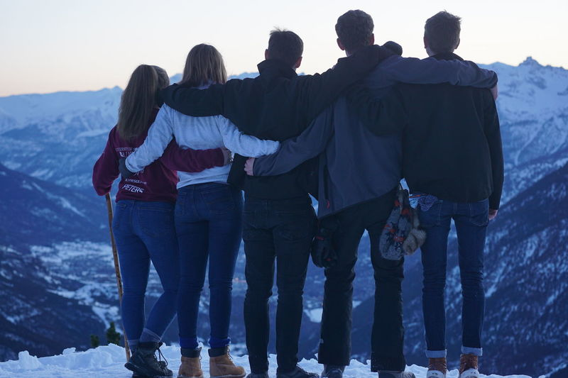 Mountain Walking Adult Arm Around Bonding Cold Temperature Emotion Friendship Full Length Group Of People Leisure Activity Lifestyles Men Nature People Positive Emotion Real People Rear View Standing Togetherness Warm Clothing Winter Women