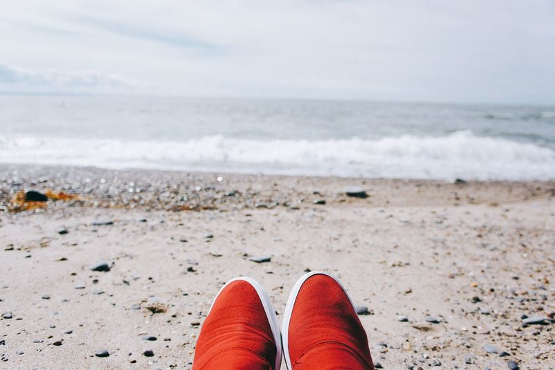 Close-up of shoes on beach against sea