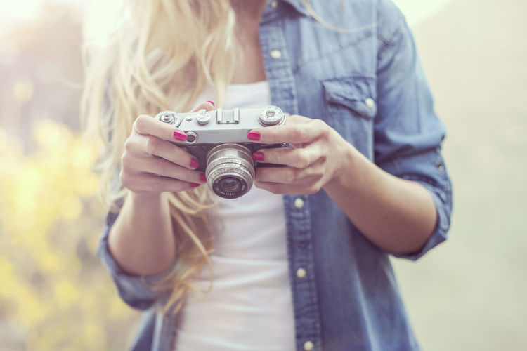 Close-up of woman holding camera while standing outdoors