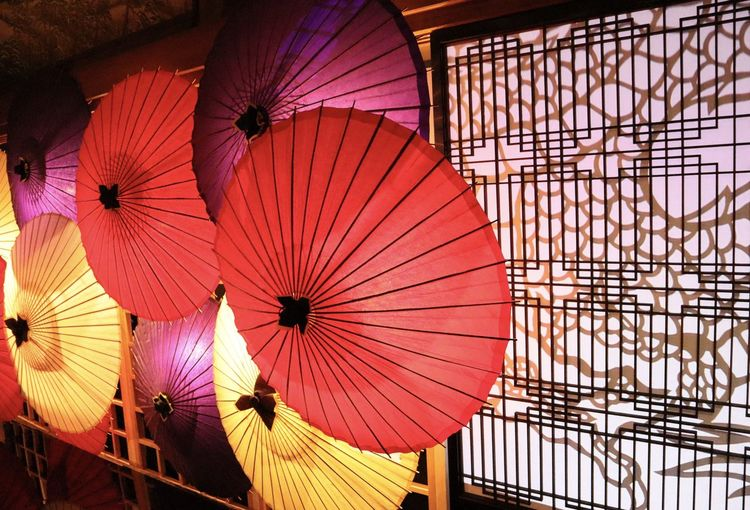 Close-up of multi colored umbrellas against wall