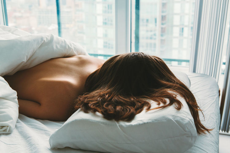 High angle view of shirtless woman sleeping on bed