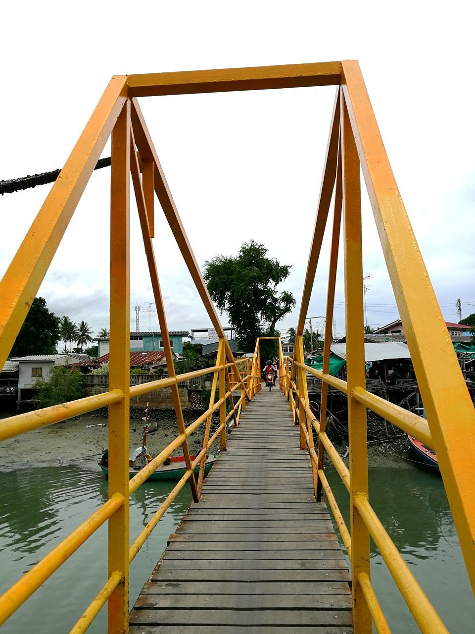 childhood, real people, built structure, leisure activity, two people, rear view, men, day, full length, bridge - man made structure, outdoors, lifestyles, sky, togetherness, outdoor play equipment, tree, playing, architecture, water, nature, adult, people