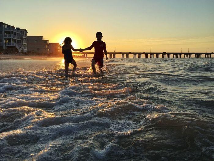 Playful Siblings Dancing At Shore Against Sky During Sunset
