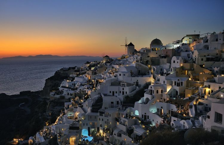 Malephotographerofthemonth Oia Santorini Greece Windmill Sunset Beach Tourism Cityscape Sunset Vacations Sea Town Architecture Building Exterior High Angle View Travel Destinations Clear Sky Water City
