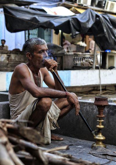 Man smoking hookah in village