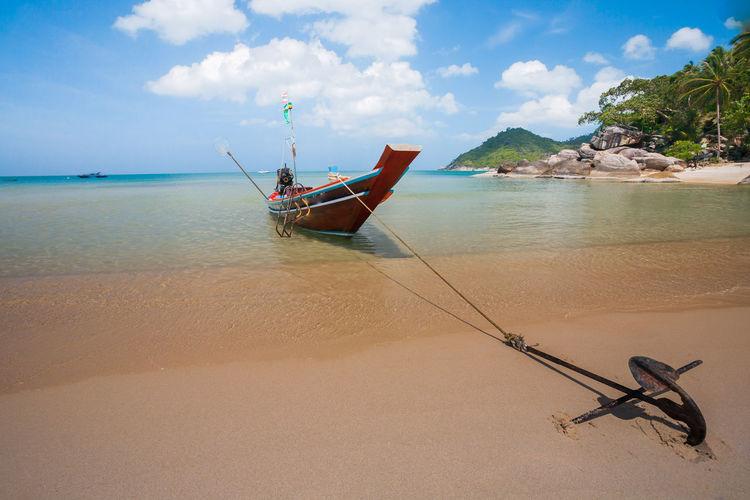 Fishing boat on beach against sky