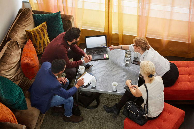 High angle view of people sitting on sofa at table