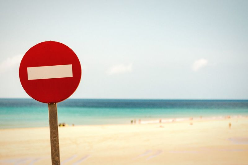 Close-up of do not enter sign at beach against sky
