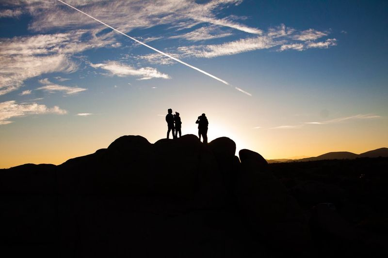 Silhouette people standing on rocks against sky during sunset