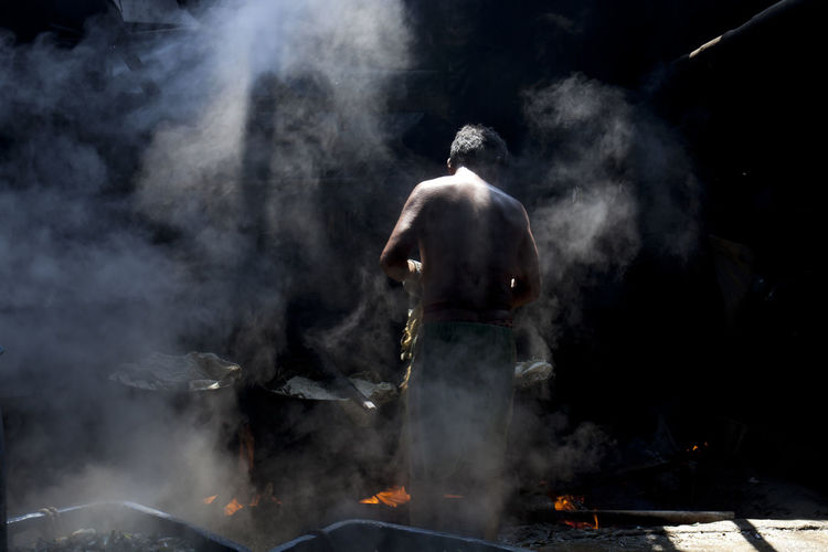 Rear view of shirtless man standing by containers over fire