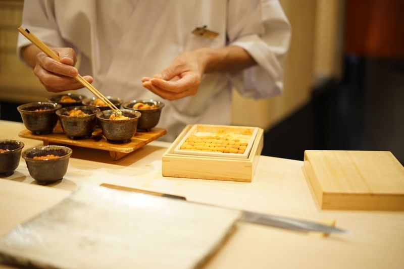Midsection of chef preparing food on table