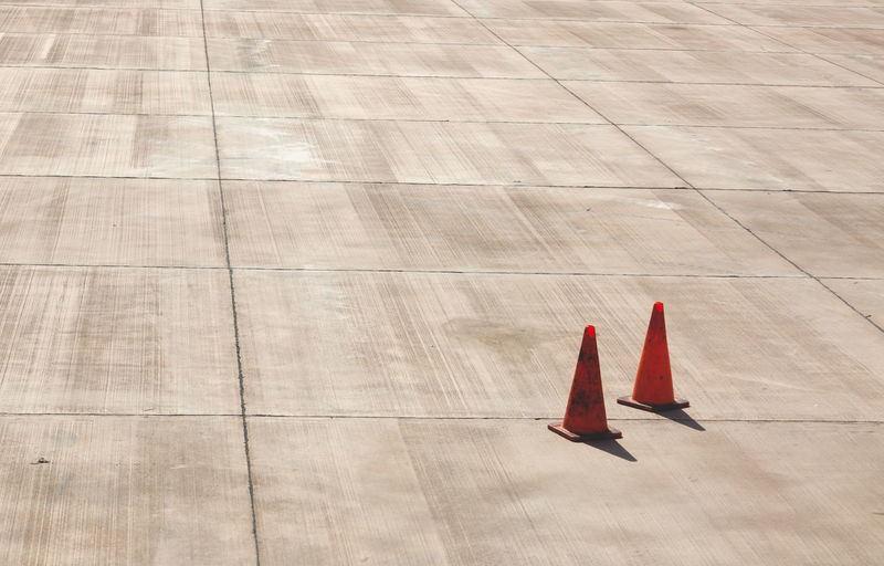 High angle view of traffic cones at concrete runway on sunny day