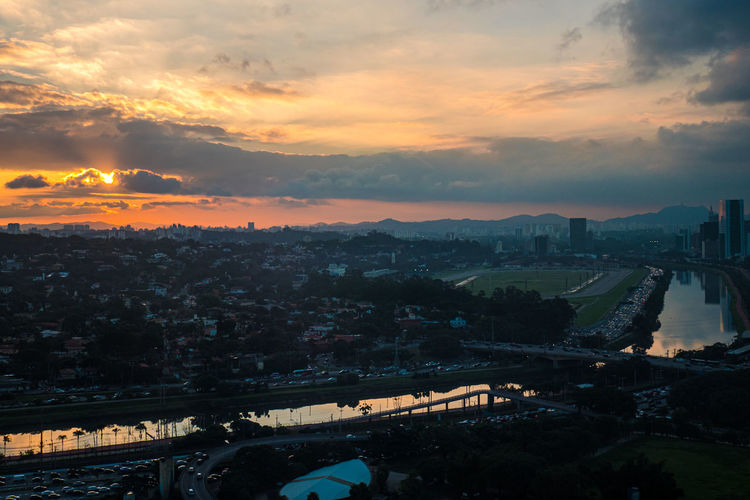 High angle view of bridge and buildings against sky during sunset
