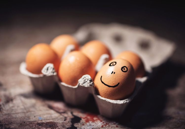Close-up of smiley face on brown egg in carton