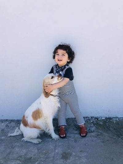 Portrait of boy with dog against sky