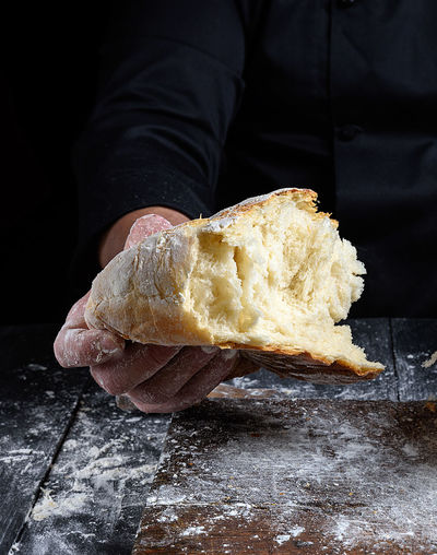 Food Food And Drink Human Hand One Person Hand Bread Freshness Human Body Part Indoors  Holding Baking Bread Dough Midsection Baked Pastry Item Close-up Table Baked Baker - Occupation Healthy Eating Preparation  Preparing Food French Food Black Background Comfort Food