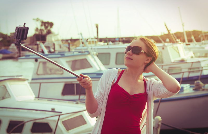 Young Woman Holding Monopod While Taking Selfie Through Smart Phone At Harbor