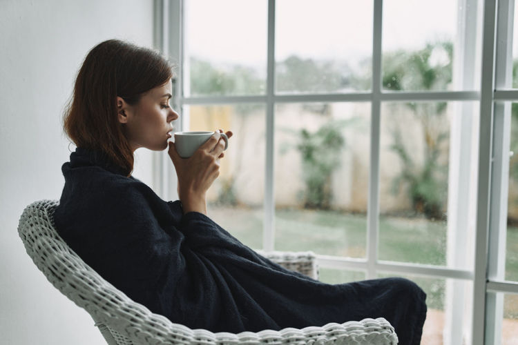 Side view of young woman drinking coffee while sitting by window