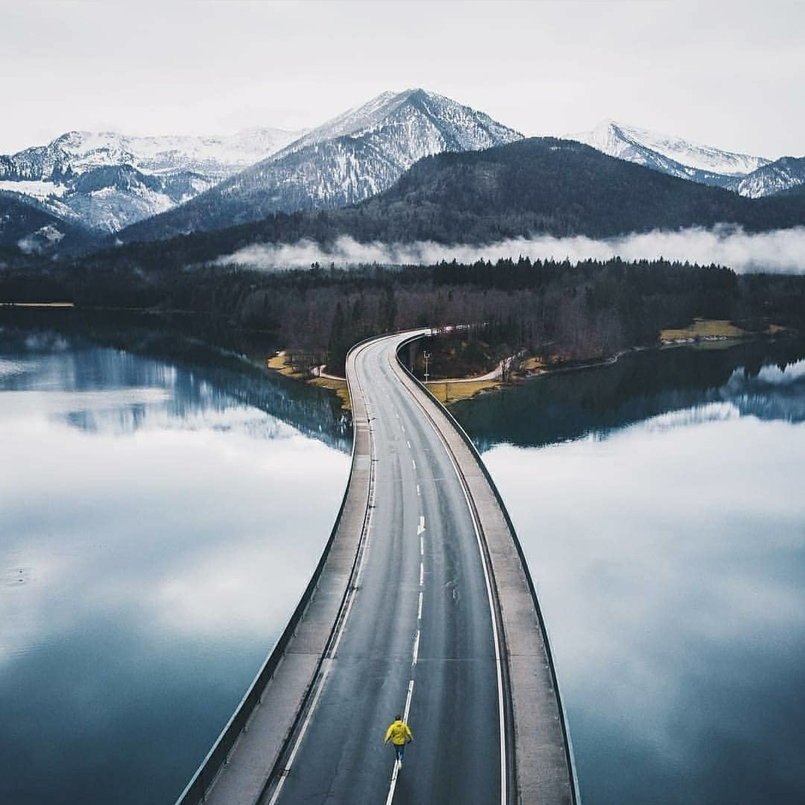 winter, mountain, snow, cold temperature, beauty in nature, scenics - nature, transportation, snowcapped mountain, nature, road, mountain range, sky, water, lake, day, non-urban scene, reflection, tranquility, no people, outdoors
