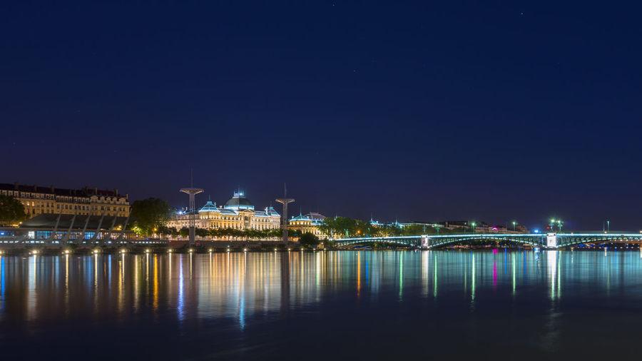 Reflection Of Illuminated Lights On River At Night