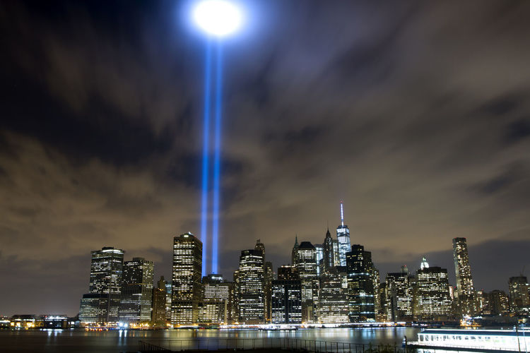 Low angle view of illuminated cityscape and tribute in light at night