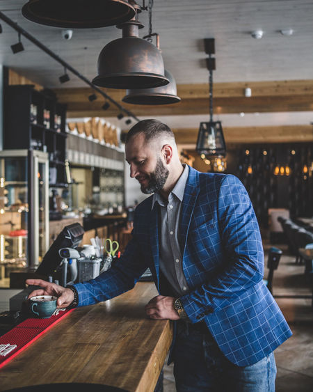 Businessman having coffee at checkout counter in restaurant