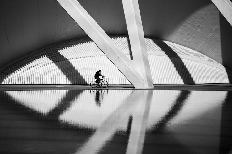 Reflection of man cycling against built structure