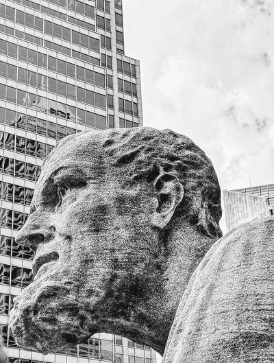 Low angle view of statue against buildings in city