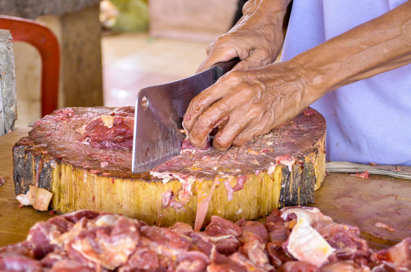 Midsection Of Man Cutting Meat On Cutting Board