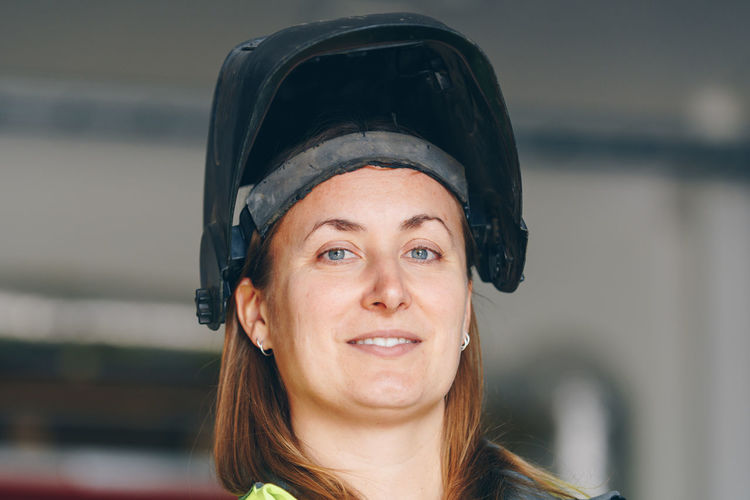 Portrait of smiling female worker wearing welding mask