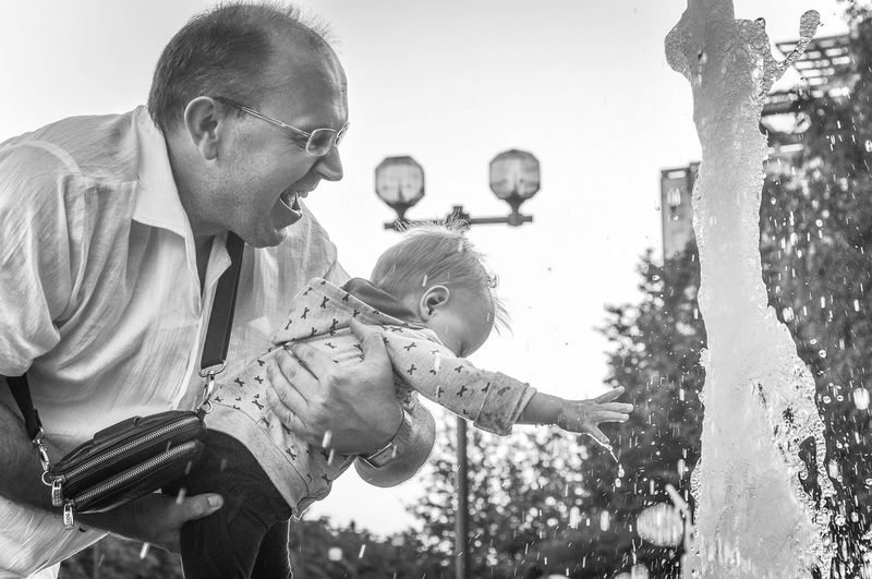 Grandfather Carrying Granddaughter By Fountain In Park