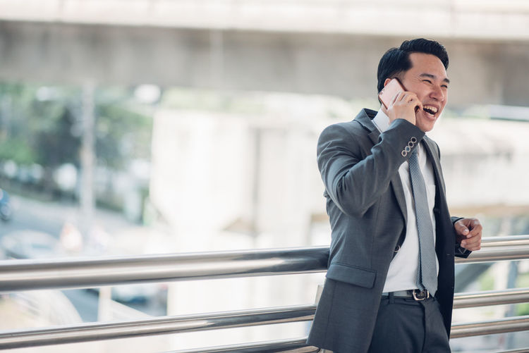 Happy businessman talking on mobile phone in office