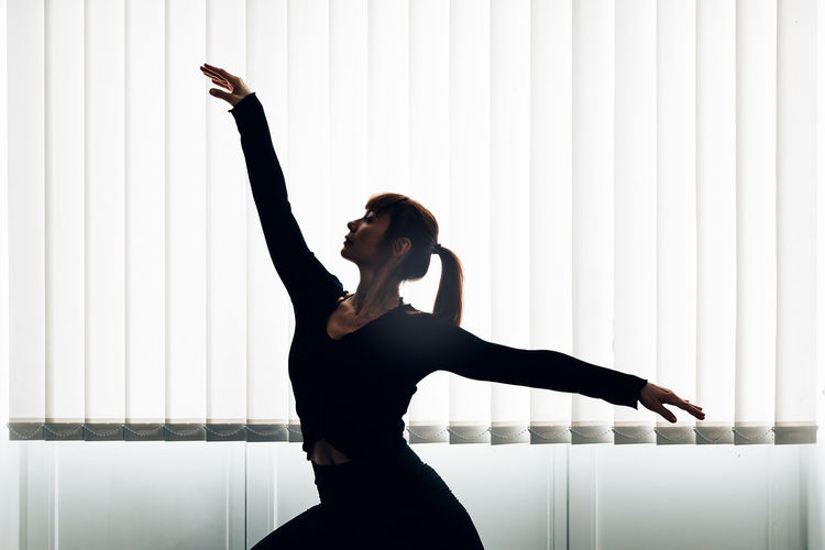 Professional dancer performing in studio under a big window.
