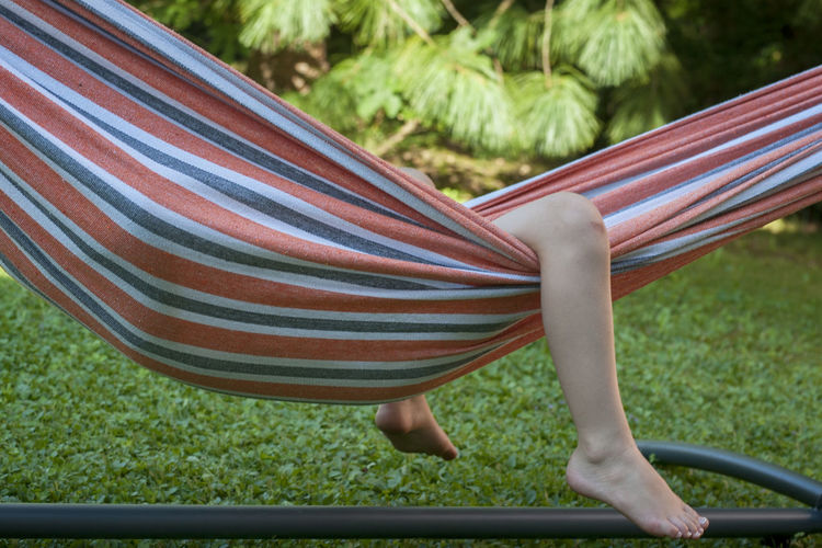 Rear view of boy lying on hammock at playground