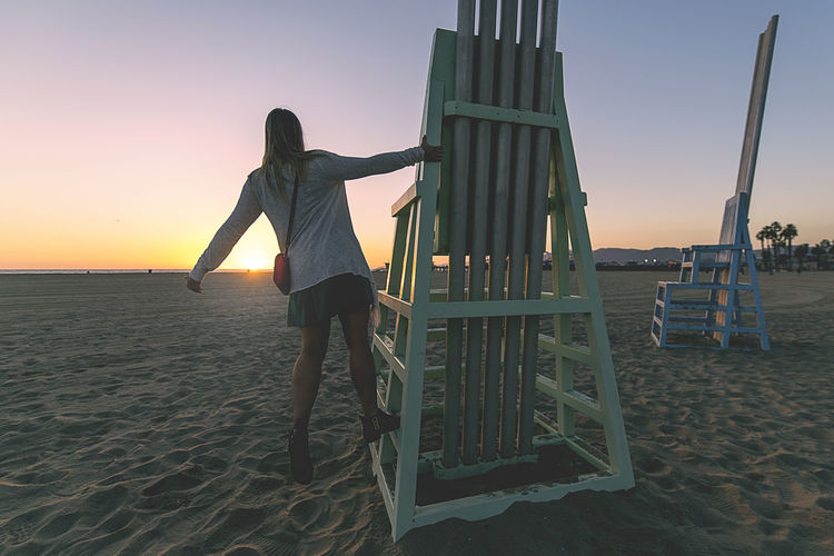 Venice Beach, California at sunset. EyeEmNewHere Sky Real People One Person Sunset Full Length Beach Leisure Activity Land Rear View Sand Lifestyles Nature Orange Color Standing Sea Playground Women Casual Clothing Water Outdoors Jungle Gym
