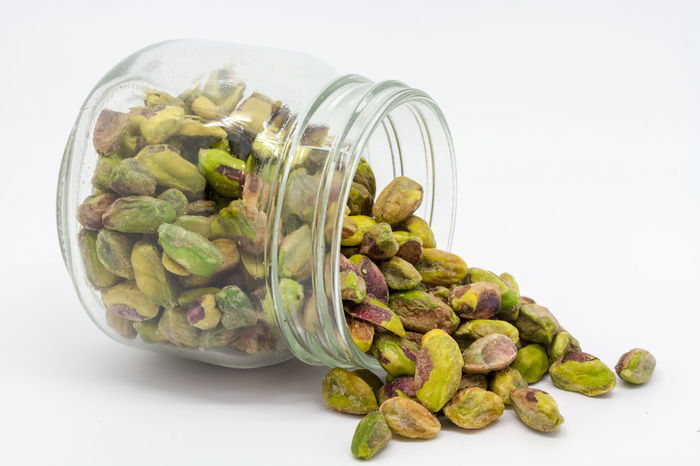 A jar of pistachio nuts Abundance Close-up Food Freshness Green Green Color Healthy Eating Jar Jar Of Nuts Large Group Of Objects No People Nuts Organic Pistachio Nuts Pistachios Raw Food Spilling Out Still Life Storage Jar Studio Shot White Background