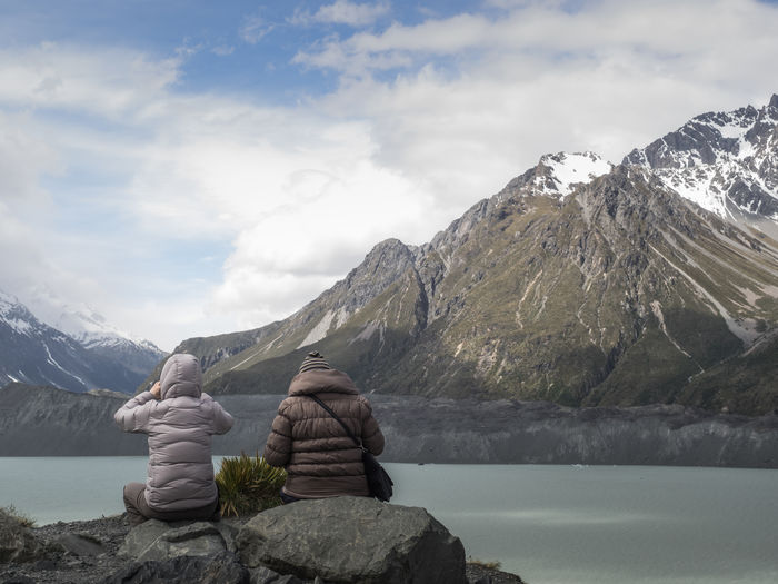 Rear View Of People Sitting On Rocks By Lake Against Mountains And Cloudy Sky