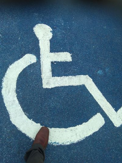 Low section of man by wheelchair access sign on road