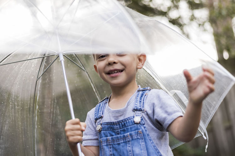 Portrait of happy boy holding umbrella while standing outdoors during rainy season