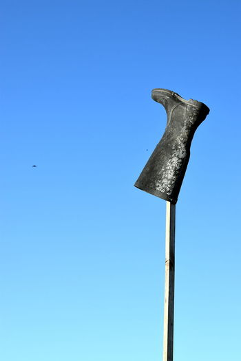 Low angle view of lizard on pole against clear blue sky