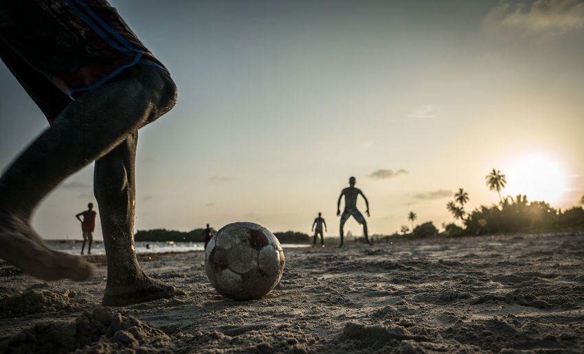 Boys playing beach soccer during sunset