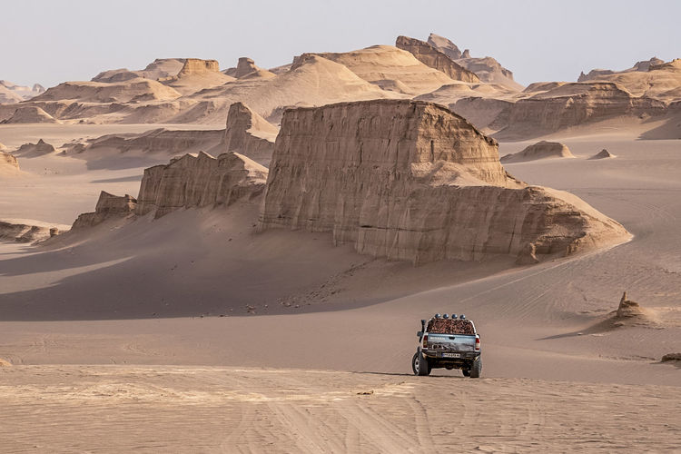 People riding motorcycle on desert against sky