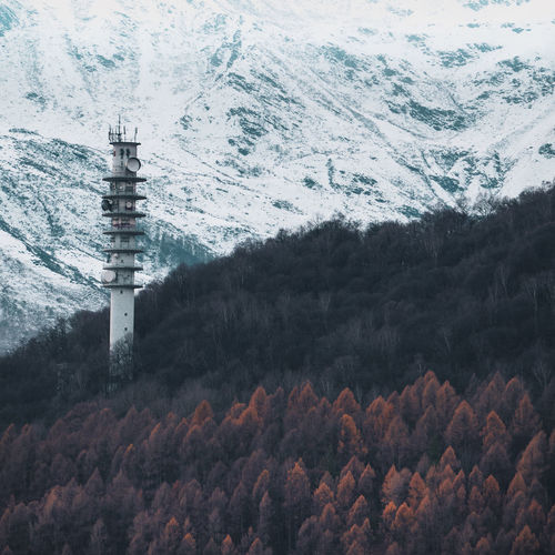 Tower against snow covered mountains