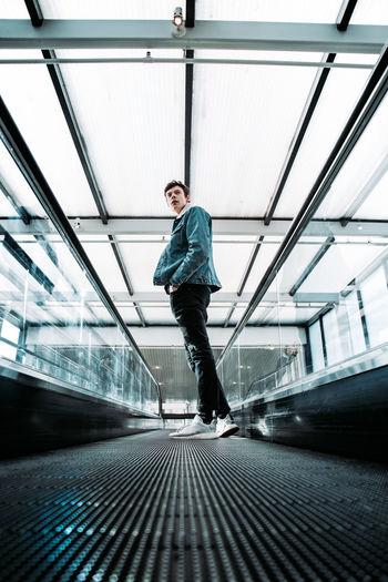 Full length of young man skateboarding on escalator