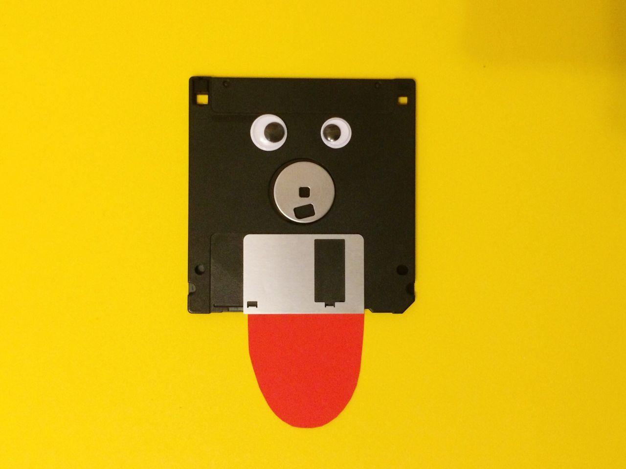 Anthropomorphic Floppy Disk Against Yellow Background