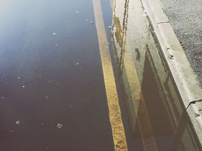 High angle view of rain water puddle on street